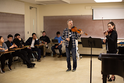 Violin student performing for class