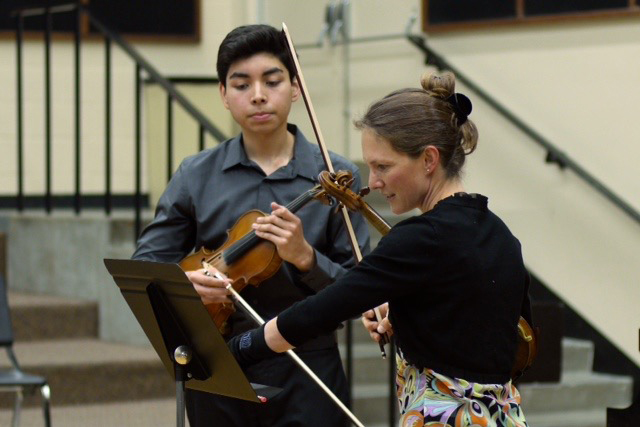 Student playing violin while teacher instructs