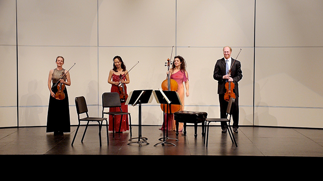Four artists on stage standing with their instruments