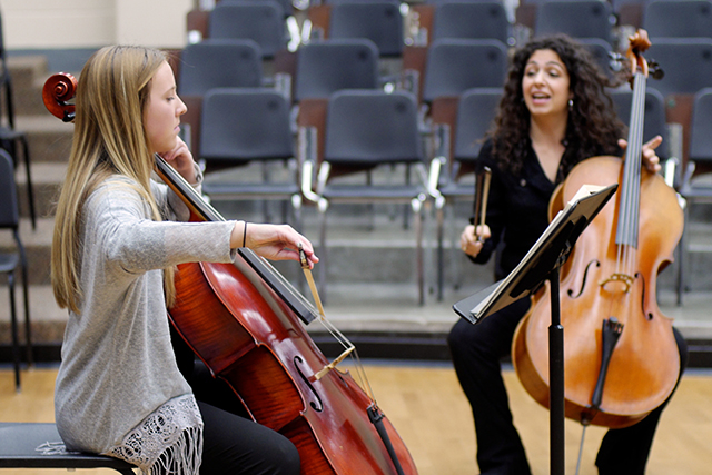 Artist with cello instructing a student