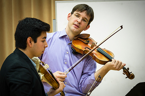 Student violinist listening while teacher instructs