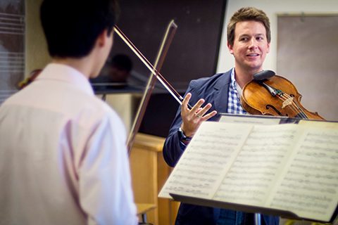 Violin instructor working with student