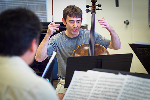 Cello instructor working with student