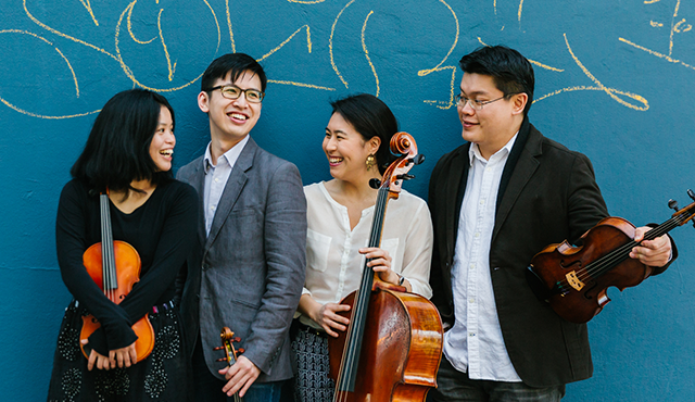 chamber music group standing in front of blue wall